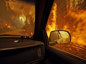 A firefighter supervisor drives through flames that jumped the road by Mark Thiessen