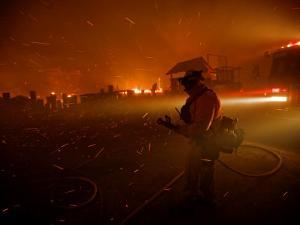A fireman watches flames advance down a hill toward local businesses by Mark Thiessen
