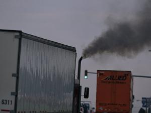 Diesel Truck Belching Exhaust from it's Smokestack at a Truckstop by Mark Thiessen