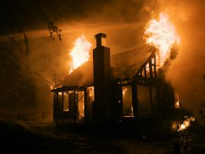 Flames engulf a house during a forest fire by Mark Thiessen