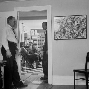 Painter Jackson Pollock Standing in Doorway Near One of His Paintings by Martha Holmes