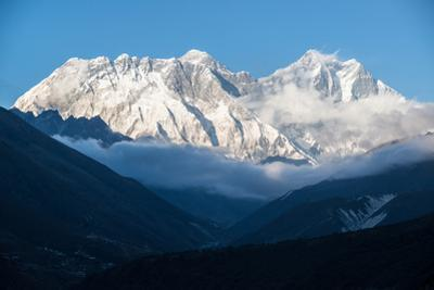 Mounts Everest and Nuptse against a blue sky. by Martin Edstrom