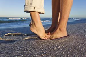 Feet of Couple Hugging on Beach by Martin Harvey