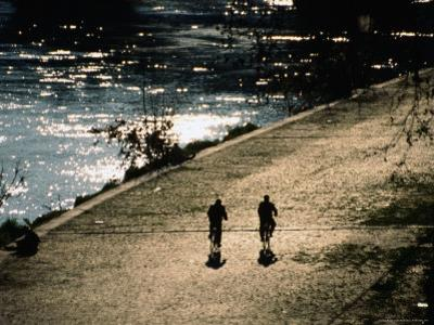 Cyclists on Cobbled River Banks of Tiber River, Rome, Italy