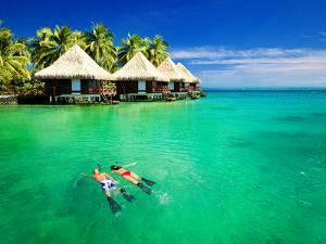 Couple Snorkling in Tropical Lagoon with over Water Bungalows by Martin Valigursky
