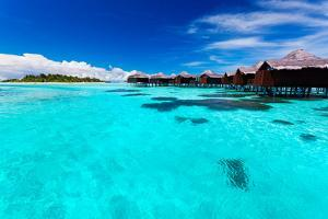 Overwater Bungallows in Blue Lagoon around Tropical Island by Martin Valigursky