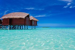Overwater Bungalow in Blue Lagoon around Tropical Island by Martin Valigursky