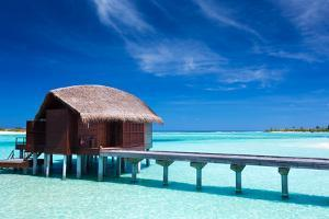 Overwater Villas in Blue Lagoon of a Tropical Island by Martin Valigursky
