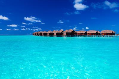 Overwater Villas in Blue Tropical Lagoon of Shallow Water by Martin Valigursky