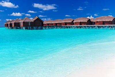 Overwater Villas in Blue Tropical Lagoon with White Sandy Beach by Martin Valigursky