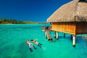 Young Couple Snorkeling from Hut over Blue Tropical Lagoon by Martin Valigursky