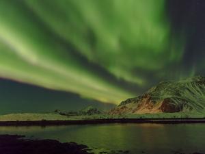 Northern Lights over Flakstadoya. The Lofoten Islands in northern Norway during winter. by Martin Zwick