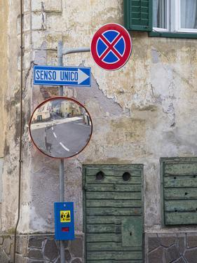 Old town house and traffic signs. Predazzo in valley Val di Fiemme, in the Dolomites Italy. by Martin Zwick