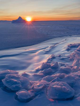 Sunset at the shore of frozen Disko Bay during winter, West Greenland, Denmark