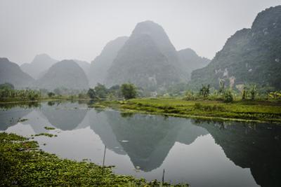 Vietnam, Ninh Binh. Limestone Karsts, with Reflection, in Fog