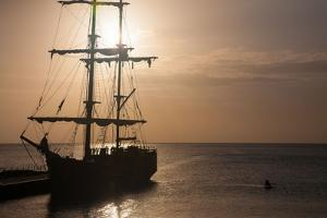 A Two Masted Brig with Furled Sails Docked in the Harbor of George Town by Matt Propert