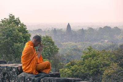 Cambodia, Siem Reap, Angkor Wat Complex. Monk Meditating with Angor Wat Temple in the Background by Matteo Colombo