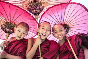 Myanmar, Mandalay Division, Bagan. Portrait of Three Novice Monks under Red Umbrellas (Mr) by Matteo Colombo