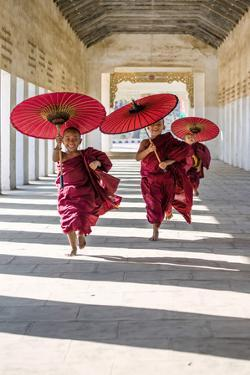 Myanmar, Mandalay Division, Bagan. Three Novice Monks Running with Red Umbrellas in a Walkway (Mr) by Matteo Colombo