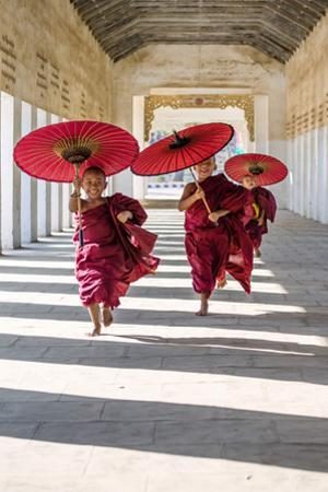 Myanmar, Mandalay Division, Bagan. Three Novice Monks Running with Red Umbrellas in a Walkway (Mr)