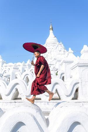 Myanmar, Mandalay Division, Mingun. Novice Monk with Red Umbrella Jumping on Hsinbyume Pagoda (Mr) by Matteo Colombo