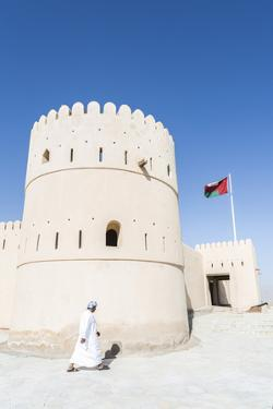 Oman, Sur. Omani Man Walking to the Entrance of Sunaysilah Old Fortress by Matteo Colombo