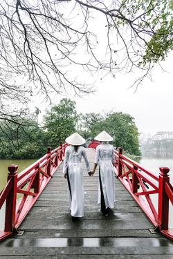 Vietnam, Hanoi, Hoan Kiem Lake. Walking on Huc Bridge in Traditional Ao Dai Dress by Matteo Colombo