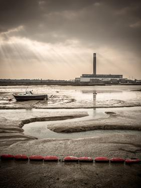 Fawley power station, a boat and a creek meandering through the mudflats all lit by a broken sky, H by Matthew Cattell