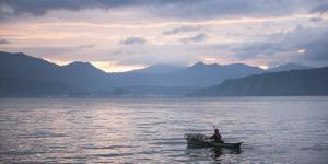 Fisherman in a Fishing Boat on Lake Toba (Danau Toba) at Sunrise, North Sumatra, Indonesia by Matthew Williams-Ellis