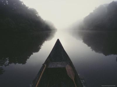 Canoe on Misty River by Mattias Klum