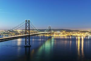 25th of April Bridge over the Tagus river (Tejo river) and Lisbon at twilight. Portugal by Mauricio Abreu