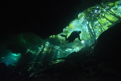 A Scuba Diver Illuminates the Way as He Explores Within the Clear Fresh Waters of Cenote Chac-Mool