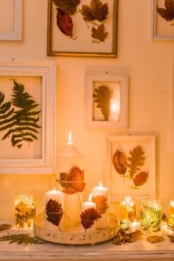 Console table, autumnal decoration, candles, picture frames, leaves by mauritius images