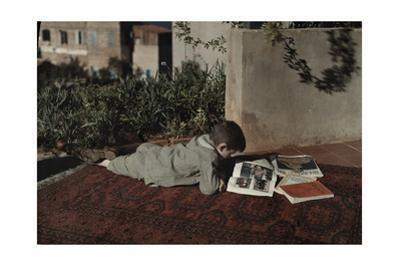 A Boy Reads a National Geographic Magazine While Lying on His Stomach by Maynard Owen Williams