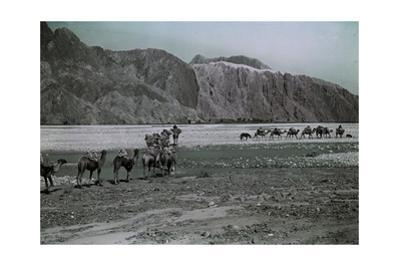 A Caravan Passes Red Cliffs in Gez Valley Enroute to the Tarim Basin by Maynard Owen Williams