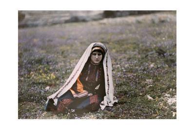 A Christian Girl in a Dark Gown Sits in a Field in Ramallah by Maynard Owen Williams