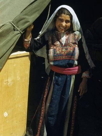 Smiling Refugee Stands at a Tent's Entrance in a Refugee Camp by Maynard Owen Williams