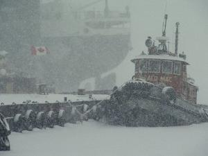 A Tugboat and Freighter at Dock in a Snowstorm by Medford Taylor