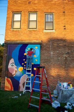 An Artist Paints a Mural on a Wall of the Matrix Theater in Mexicantown by Melissa Farlow