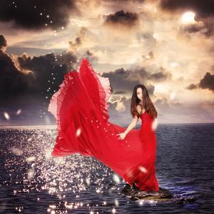 Girl in Red Dress Standing on Ocean Rocks by Melpomene