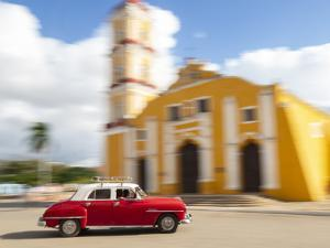 Cuba, Remedios, classic red car in front of Cathedral. by Merrill Images