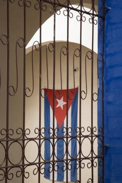 Cuba, Vinales, Cuban flag in courtyard and wrought iron gate. by Merrill Images