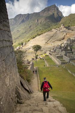 Man Walking Down Stone Steps of Machu Picchu, Peru by Merrill Images