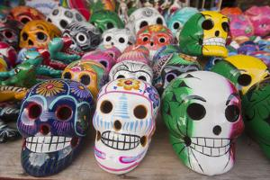 Mexico, Yucatan, Isla Mujeres, colorful ceramic calavera skulls for sale in market. by Merrill Images