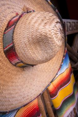 Mexico, Yucatan, Isla Mujeres, straw hat and colorful blankets. by Merrill Images