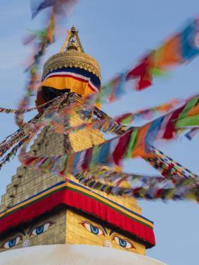 Nepal, Kathmandu, Swayambhunath Stupa and fluttering prayer flags in motion by Merrill Images