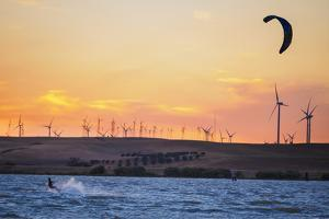 Usa, California, Rio Vista. Kiteboarder at sunset with wind farm turbines. by Merrill Images