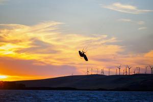 USA, California, Rio Vista, Sacramento River Delta. Kiteboarder catching air at sunset. by Merrill Images