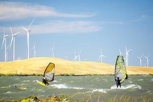 Usa, California, Rio Vista, Sacramento River Delta. Sailboarders with wind turbines. by Merrill Images