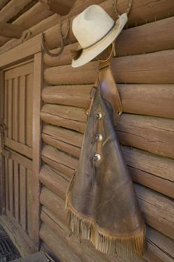 USA, Montana, Livingston, cowboy hat and chaps hanging on barn wall. by Merrill Images